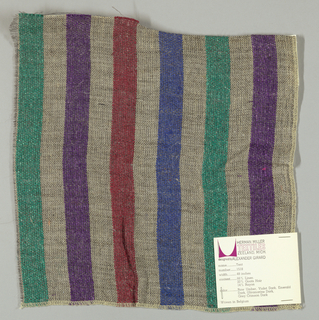Plain weave of variegated grey and violet, dark red, blue and green vertical stripes. The grey striped areas are comprised off-white warps while the wefts are comprised of white threads loosely twisted with black goat hair. The violet, dark red, blue and green stripes are made of heavier warp threads with a slight sheen.