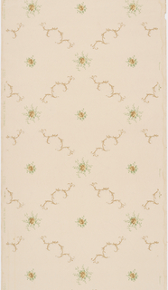 Thin foliate scrolls create large trellis pattern of diamond shaped cells.  A rose blossom surrounded by leafy sprays sits at the center and four intersecting points of each diamond cell. Roses are printed in beige, leaves in light green, foliate scrolls in metallic gold on tan background.