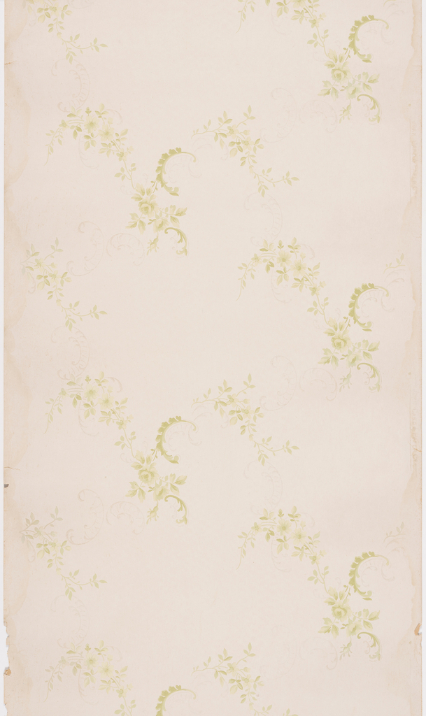Staggered pattern of floral sprays with prominent crescent-shaped branch of leaves are placed on the diagonal and connected to each other by a faint pattern of scrollwork. Design is printed in beige over a tan ground.