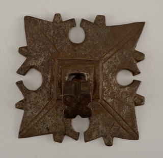 Flat, square mount with square molded element rising at center and paired radiating lines. Each quadrant of design has a projecting cusp and four barbs forming a leaf-like pattern. Grooved nail heads on a square shank.