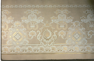 Flitter frieze, with circular floral medallions alternating with Rococo-revival medallions. Printed in white,metallic gold, and gold mica flakes on tan ground.