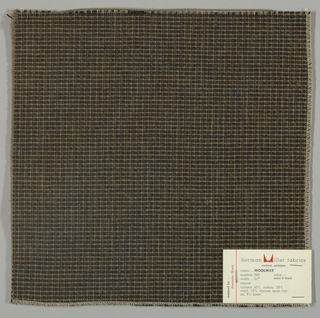 Textured plain weave in black, grey and brown. Warp is comprised of heavy black and grey yarns and shiny threads in brown. Weft is comprised of thick grey yarns.