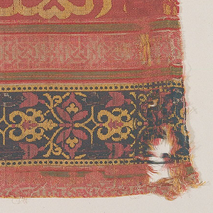 Satin ground vertically striped in rose-red, orange-red, dark blue, green and white.  A broad rosy-red stripe at left has a large-scale Arabic inscription in yellow (the fabric must be turned 90 degrees in order to read the Islamic inscription). The central white stripe has geometric knot-like design in red (so badly worn that design is almost indistinguishable); the dark blue stripe on the right has arabesques in yellow and red.  Narrow white, green, and orange-red stripes border the wider stripes described above.  No selvedge present.