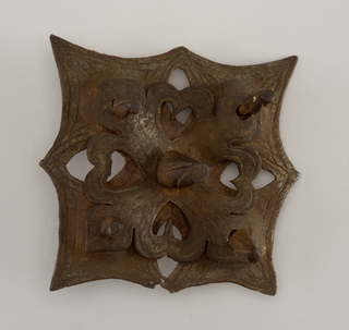 Square pierced and repousséd mount of four cusps with wrought border-lines, surmounted by a second squared and pierced plate wrought into a four-quadrant design of trefoil leaves. Nails have tall spiraled conical heads on squared shanks.
