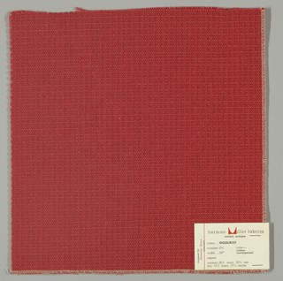 Textured plain weave in dark red. Warp is comprised of heavy yarns and shiny threads in dark red. Weft is comprised of thick and thin yarns in dark red.