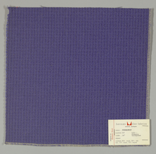 Textured plain weave in blue-violet. Warp is comprised of heavy yarns and shiny threads in blue-violet. Weft is comprised of thick and thin yarns in blue-violet.