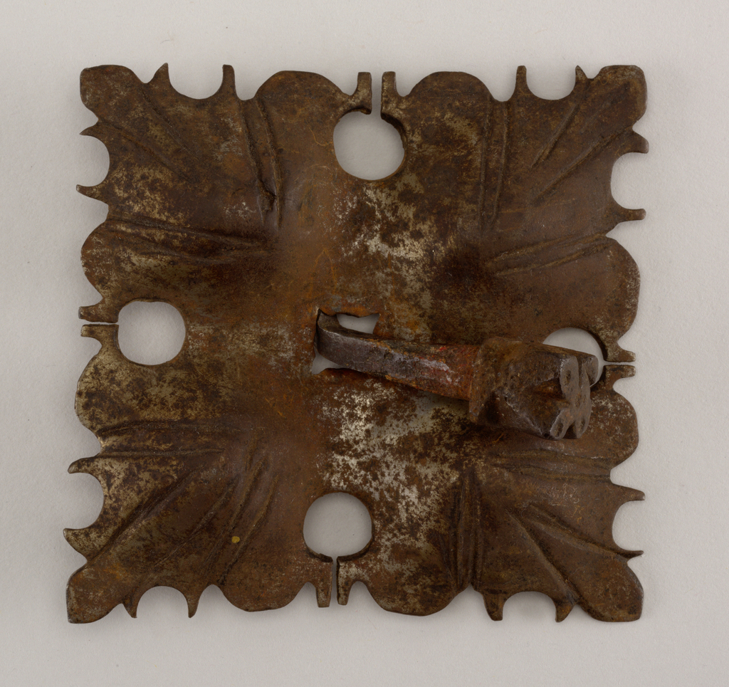 Square pierced and shaped mount, hammered and wrought lines at four corners to form quadrated designs of leaf-like elements. Nail with notched square head and square shank.