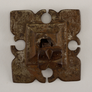 Flat, square mount with square molded element rising at center. Each quadrant of design has a projecting cusp and two barbs forming a leaf-like pattern. Grooved nail heads on a square shank.