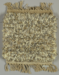 Hand woven in high pile in tones of white, grey and beige.