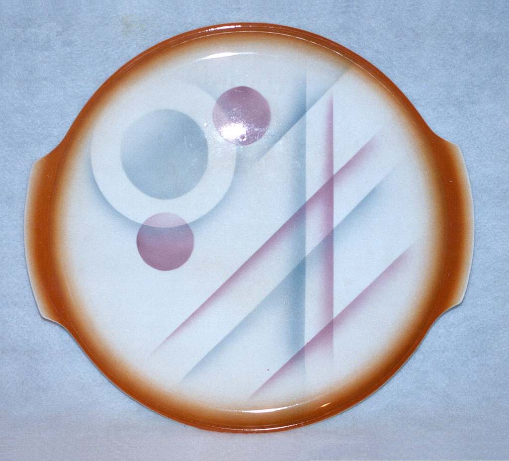 Circular concave plate with bracing tab handles and raised bottom rim.  White background with airbrushed orange lining the edge and the tabs.  Abstract airbrushed design of blue and lavender circles and intersecting lines.