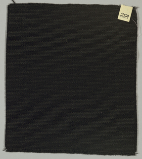 Warp-faced plain weave in black. Warp is comprised of black threads while the weft is made up of heavy black yarns.