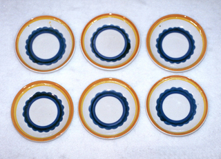 Circular concave dish.  Cream background with concentric circles from edge to center of: orange, yellow, cream, royal blue with a scalloped edge, dark blue, royal blue, and finally a round cream center.
