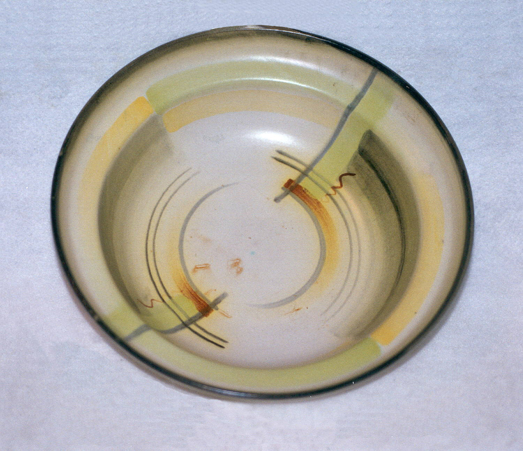 Circular dish with raised bottom rim and curving wide lip.  Light yellowish ground color with a black edge.  Airbrushed design over the surface of yellow and light green bands, gray lines, and brown splashes and squiggles.