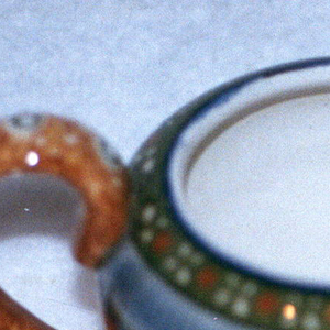 Circular form with inward curving lip.  Spout coming out of the body across from a c-shaped handle.  Blue lines the top and bottom edge. The form is decorated in three bands.  First, a green background with white and orange stylized blossoms.  Next, a band of gray with blue vertical lines.  Finally, a brown ground with white and green circles that also patterns the handle and spout.