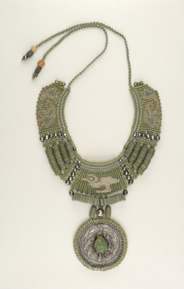 Small woven and beaded collar, grayish-green hues, stylized bird stitched on central panel; large Chimu silver disc with knotted? border, mask bead center.