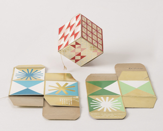 Three collapsible cube-shaped ornaments printed with linear geometric decoration on gold foil ground: -7a in red, pink, and white; -7b in green and white; -7c in blue and white; gold cord hanger on each box. One flap on each box with instructions.