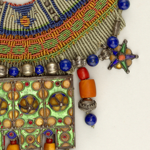 Bib form collar of purple, red, green, gold, silver hues; large enameled silver pectoral ornament suspended center, smaller beads hang from lower edge.
