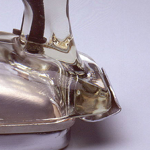 """Broad, oblong wedge-shaped profile comprising one-piece molded transparent glass shroud and handle affixed to white metal soleplate and heel rest. Fabric-covered power cord emerges from tubular rubber flange at top right side. Black plastic dial on red face-plate inscribed:  """"Off, On, Rayon, Silk, Wool, Cotton, Linen,"""" and """"Low, Med, High."""""""