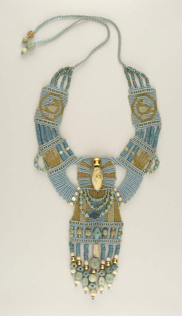Bib form collar, woven, blue, tan, gold; gold and ceramic beads intersperced; central bead in form of head; fringe of seven long strands of beads lower edge.