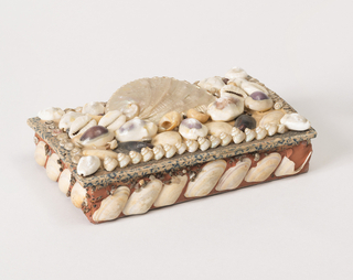 Rectangular box with lid hinged in gauze.  Inside and outside covered with white paper printed with small blue flowers. On sides, a row of diagonally set shells; on lid, a large haliotis shell surrounded by a multitude of smaller shells of varying kind.