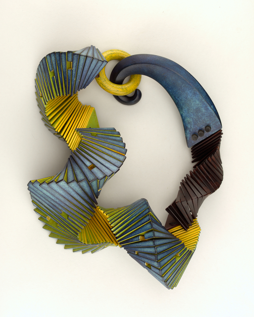 Twisted wooden neckpiece painted blue, black, brown, and yellow. One end in blue reminiscent of a curled tail or an elephant trunk; other end has a ring.