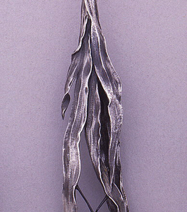 Handle in the form of a patinated spider on spider's web suspended between blades of grass.