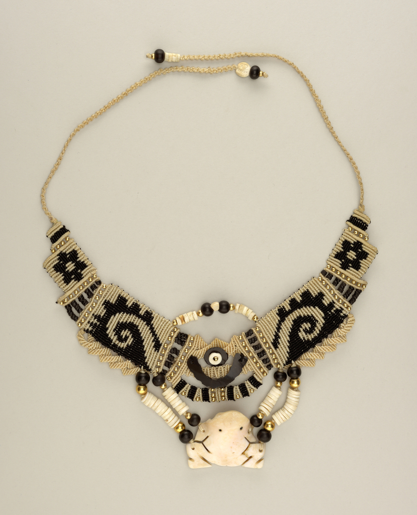 Choker of woven black and white thread, gold and obsidian beads; pendant in the form of a stylized frog hangs from cords strung with shell, gold, and obsidian beads.
