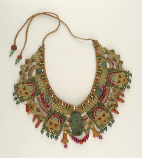 Flat, woven, beaded collar with tan, green, deep rose colors; beads intersperced; panels with masks; bronze figural pendant, greenish patina, lays on collar at center.