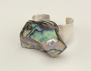 Adjustable hand-wrought cuff style silver bracelet featuring a large piece of abalone and a baroque pearl.