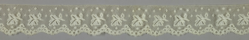 Design of separate leaf motifs with dots above a border of flower motifs arranged to form scallops.