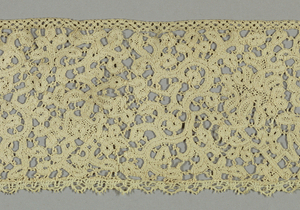 Border with a pattern of elaborate, intertwining narrow branches accented by blossoms at intervals.