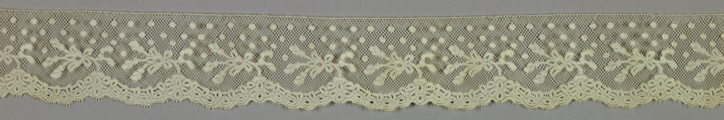 Detached ornaments and dots on diamond-shaped mesh; scalloped border.