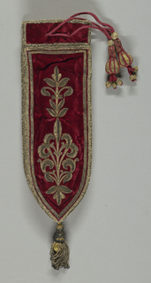 Knife case in red velvet embroidered with gold metallic yarns in a stylized floral form. Gold braid on the sides and top, with a drawstring at the top terminating in beaded tassels, with a single gold tassel at the bottom.