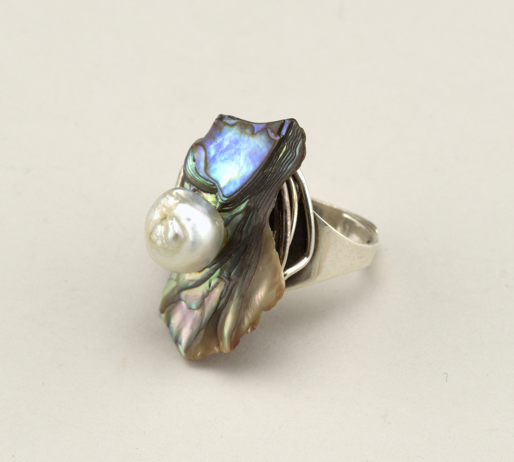 Adjustable hand-wrought silver ring featuring a piece of abalone and a baroque pearl.