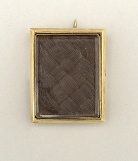Rectangular plain gold frame surrounding a panel of braided, brown hair, shown under glass.