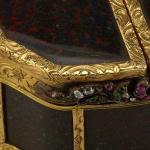 Pouch shape, with two hinged covers and two compartments; plaques of heliotrope held in a frame of gold carved with scrolls, leaves and pinecone motifs; thumb-piece of foliate scrolls set with small diamonds, rubies, and emeralds; sides of box lined with gold.