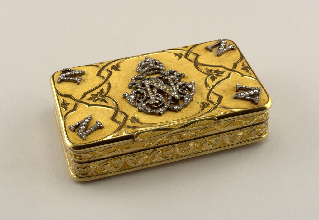"A gold box with a personalized lid. The letter ""N"" in each of the lid's corners in diamonds. The center of the lid is decorated with another larger letter ""N"" in diamonds with a diamond crown above the letter. Along the sides of the box there is an abstract design carved in gold."