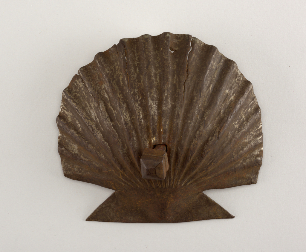 In the form of a scallop shell. Squared nail head on squared shank.