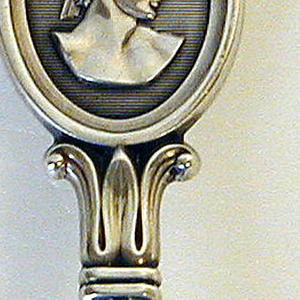 Antique style bust at tip of handle; circular fluted bowl with piercing.