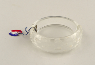 Hinged cuff of clear plastic decorated with bands of small matte elipses.