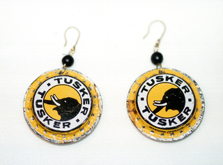 """Each earing a slightly flattened bottlecap showing a black elephant head in profile within a white circular band with """"Tusker"""" above and below, all on a yellow ground; suspended from shaped wire with one black glass bead."""