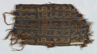 Thick border with two selvedges (or loom ends?) Pattern of narrow bands of kufic inscriptions, all alike but in different color combinations: brown on tan, blue on orange, blue on red.