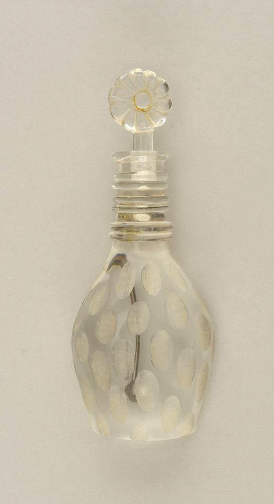 Clear brooch in the form of a decanter and stopper.