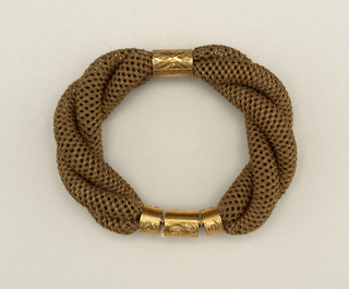 Bracelet composed of three twisted woven tubes of brown human hair. Central mount of gold engraved with lozenges. Ends with three-part clasp of gold in form of articulated tube. Central part of clasp fitted with loop.