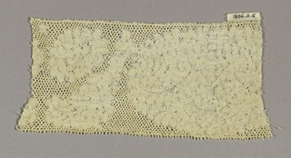 Straight-edged fragment with Valenciennes ground in a large, solidly massed floral design.
