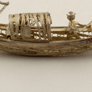 Silver gondola with cabin and two rowers.  The cabin, which is hinged at the back, contains a seat and a swinging door.