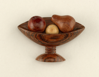 Brooch in the form of a footed bowl holding three pieces of fruit.