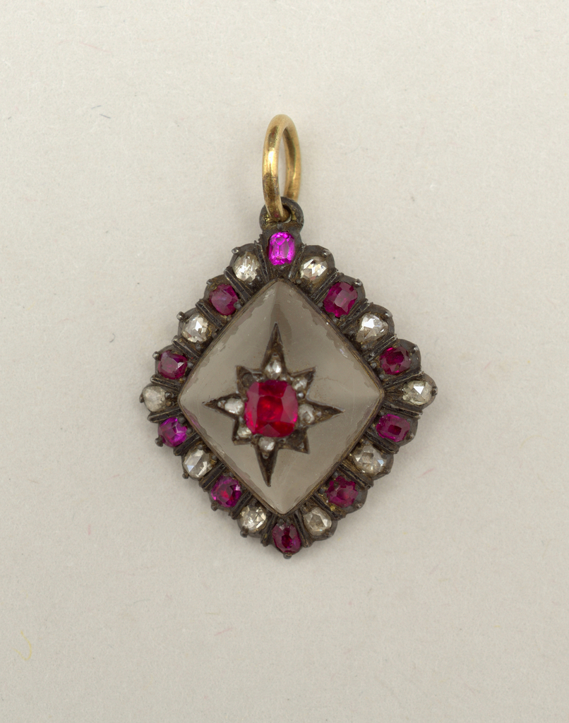 Lozenge-shaped glass with ornamental star of red and white stones in center; border of red and white stones set in gold; gold ring at top.