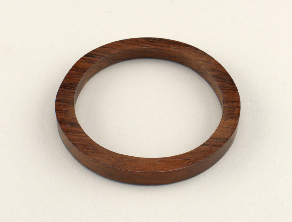 Dark brown circular form with slightly irregular contours.
