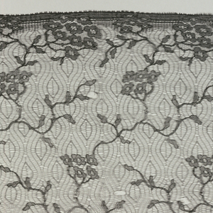Oblong black veil with a ground of very open net showing an ogival pattern with a design of flower sprays worked in the border along the lower edge.